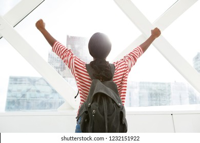 Portrait from behind of young travel woman with arms raised by the city