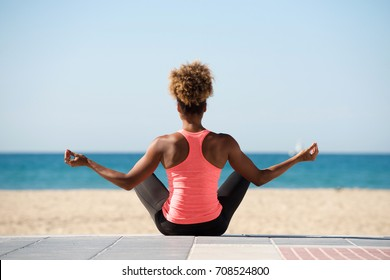 Portrait from behind of young woman doing yoga exercise on seaside