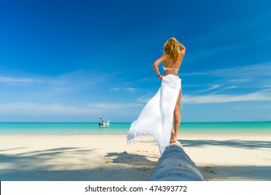 Portrait from behind of young woman walking to the water on the beach