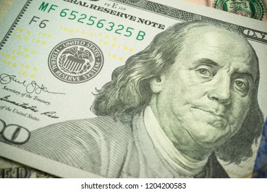 Portrait of Benjamin Franklin president and Federal Reserve System (FED) seal macro detail on a hundred dollar banknote or bill. Concept of central bank and USA or world economic financial.