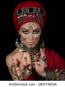 Portrait of berber woman with marks on her face in red turban on black background