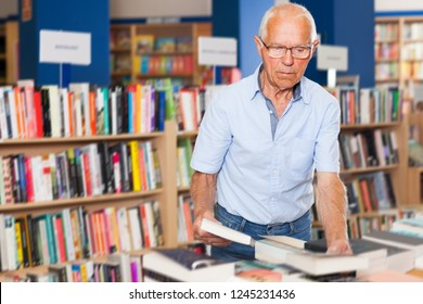 Portrait of bespectacled senior male customer visiting bookshop in search of interesting fiction