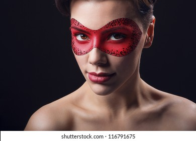 portrait of beutiful woman in red leather mask on dark background