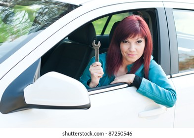 Portrait of a bewildered young woman sitting in a car outdoors with a wrench in her hand
