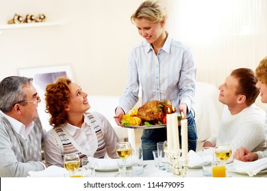 Portrait of big family sitting at festive table and looking at pretty woman with dish of roasted turkey