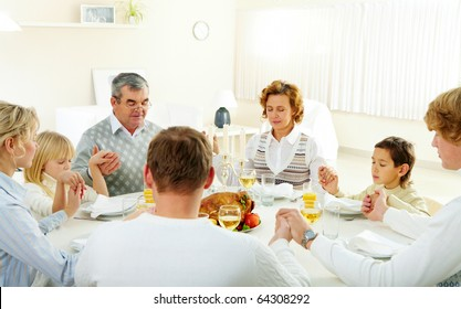 Portrait of big family sitting at festive table and holding each other by hands while praying