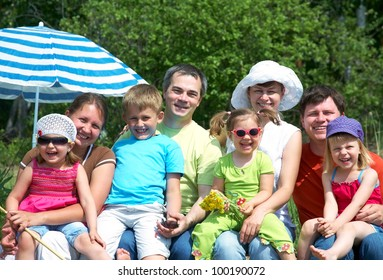 Portrait of big family  with their little daughter under beach umbrella