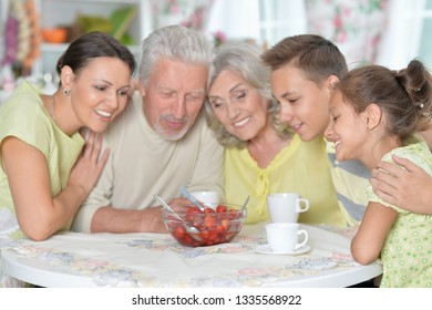 Portrait of big happy family eating fresh strawberries at kitchen