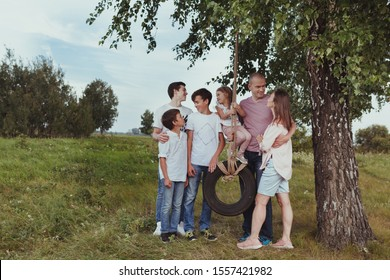 portrait of a big happy family on a background of summer nature, a walk in the field