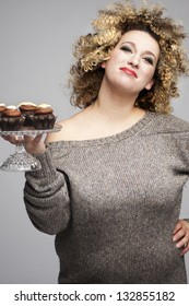portrait of a bigger woman holding muffins