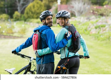 Portrait of biker couple with mountain bike in countryside