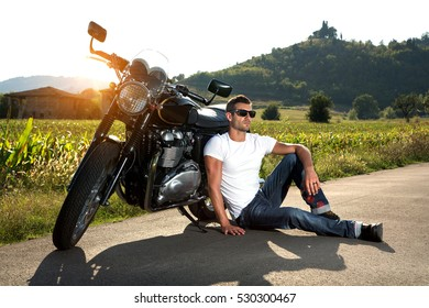 Portrait of biker man wearing a white shirt, blue jeans and sunglasses sitting on the street looking at the sunset with the sun behind his classic motorcycle