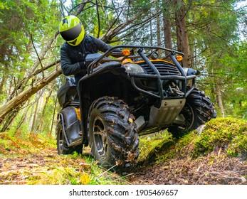 Porträt eines Fahrers auf einem ATV. Fahrradfahrer fahren im Wald. Er sieht sich Räder von Quadbike an. Fahrrad auf dem Hintergrund des Waldes. ATV-Fahrer in grüner Taiga. ATV als Symbol für Extremsport.