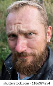 Portrait of a biker with a wet beard and an earring in a leather jacket outdoors