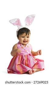 Portrait of a biracial baby dressed in pink and giant bunny ears.