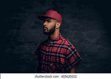 Portrait of Black bearded male dressed in a red fleece shirt and a cap over grey background.