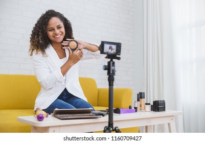 Portrait of black blogger woman review giveaway make up gift to fan following channel while recording video makeup cosmetic at home online influencer vlogger girl social media live steaming concept