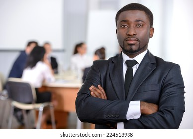 Portrait of black businessman, people group in background at modern bright office indoors