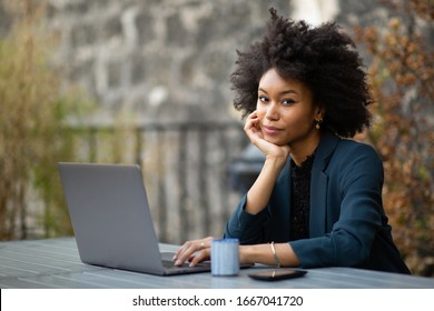 Portrait black businesswoman sitting with laptop computer