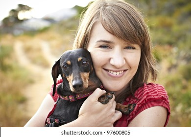 Portrait of a black Dachshund dog and young lady on sand path