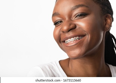 Portrait Of Black Girl In Dental Braces Smiling To Camera Posing On White Background. Orthodontics Concept. Studio Shot, Free Space