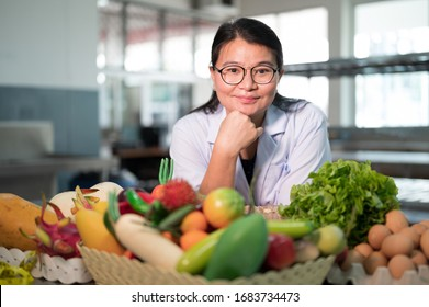 Portrait black long hair Asian pretty young woman nutritionist smiling with out of focus vegetables, fruits and eggs in the kitchen.The chef is thinking of creating a menu.
