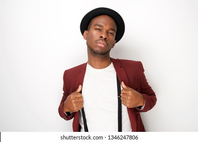 Portrait of black male fashion model posing with hat and suspenders by white background