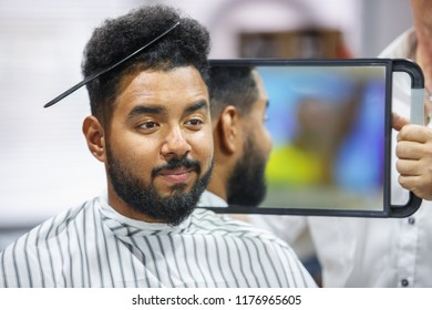 Portrait of black man with comb in curly hair looking in the mirror to the check haircut.Barber showing client his work in barbershop salon.Male beauty treatment concept