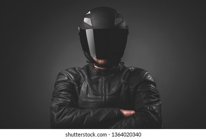 Portrait of black motorcyclist with helmet on dark grey background. Low light
