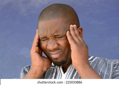 Portrait of a black South African young man with a headache and a sick facial expression holding his head with his hands. Image on a blurry blue dirty wall background.