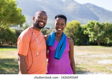 Portrait of black sporty couple looking at camera at park with copy space. Happy mature man and smiling woman relaxing after jogging in the park. African american man and woman resting after exercise.