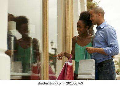 Portrait of black tourist heterosexual couple in Panama City with shopping bags. The man and his girlfriend look at shop window