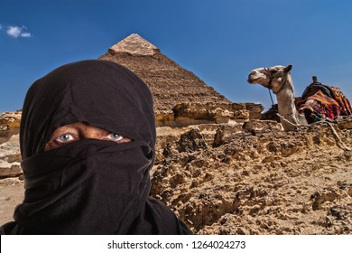 portrait of a black veiled woman with camel and ancient pyramid in Egypt, Arica