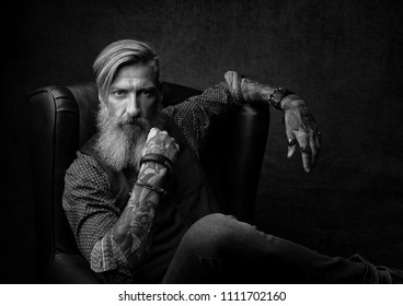 Portrait in black and white of a cool bearded businessman, who sitting on an armchair