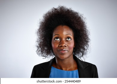 Portrait of black woman with curly hair looking up against white background