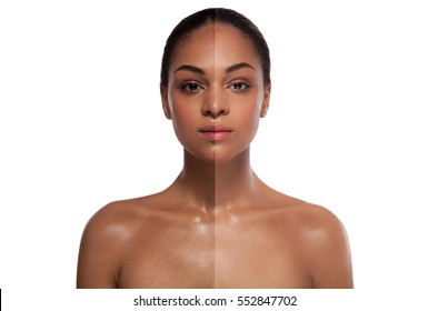 portrait of a black woman with a half of a face with a whitening skin over white background
