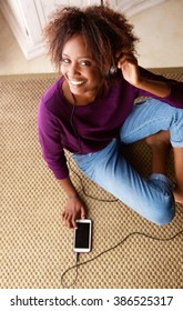 Portrait of a black woman smiling with smart phone and headphones