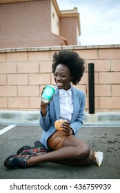 Portrait of black woman smiling while eating fast food and drinking soda on floor on parking lot