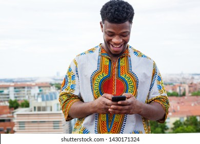 portrait of a black Young man wearing african traditional colorful clothes using smartphone while smiles on an european city rooftop background. Having fun using dating apps or chatting.