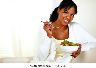 Portrait of a black young woman looking at you as she eats her green salad at home indoor. With copyspace.