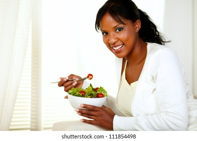 Portrait of a black young woman smiling and eating a green salad and looking at you.