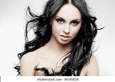 Portrait of a black-haired beauty on bright background
