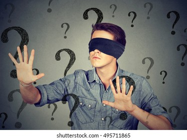 Portrait blindfolded man stretching his arms out walking through many question marks isolated on gray wall background