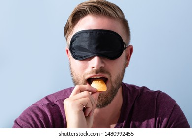 Portrait Of Blindfolded Young Man Tasting Food