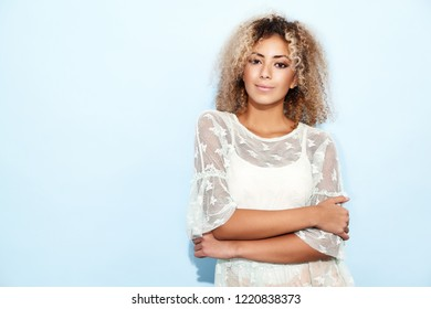Portrait of blissful lovable woman with blond african hairstyle. Smiling model girl in trendy summer clothes posing on blue background