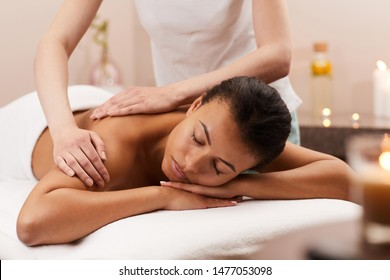 Portrait of blissful young woman enjoying massage in luxury SPA, copy space