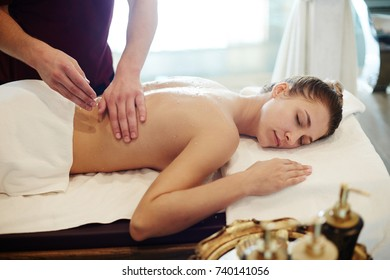 Portrait of blissful young woman enjoying massage in SPA center, lying on massage table with eyes closed and smiling with male masseur rubbing her back