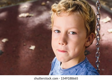 Portrait of blond boy of 6 years with funny face of rogue.