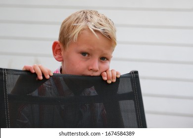 Portrait of a Blond Boy with sad eyes hiding behind a chair