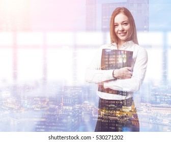 Portrait of a blond businesswoman hugging a folder and standing in her office smiling. City is seen in the foreground. Mock up. Toned image. Double exposure